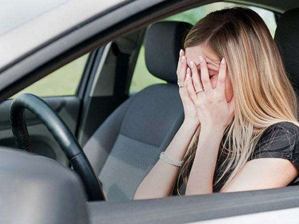 Distraught woman in car  who needs car odor removal service image.